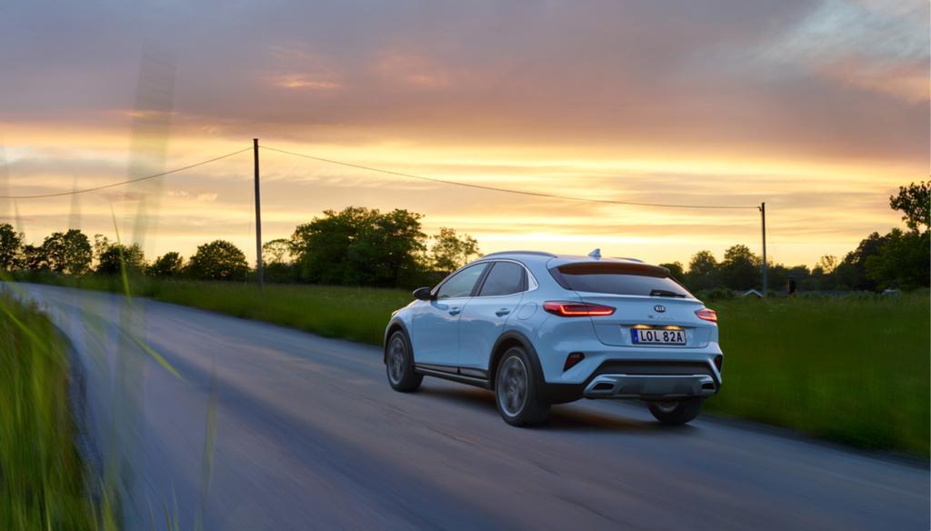 En Kia XCeed Plug-In Hybrid som kör på landsväg under sommarkvällen